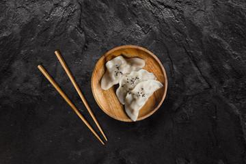 Plate of Asian gyoza dumplings on black slate stone.