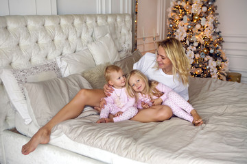 mother with two daughters in their pajamas sitting on the bed in the new year