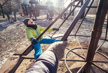 Deep autumn on child playground. Boy turns on the carousel
