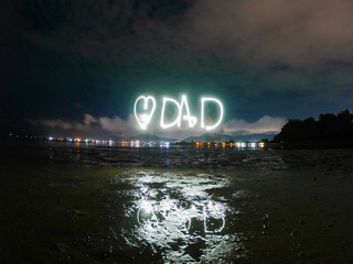 love dad text word for father 's day , made from sparkle  light paining in the dark night , motion with long exposure .