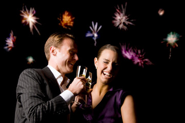 Couple Toasting At Party With Fireworks In Background