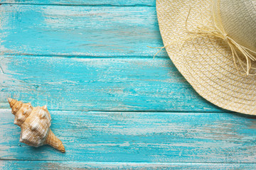 Straw hat and a  seashell on a painted blue paint vintage boards The top view. Close-upThe top view. Close-up
