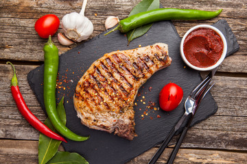 Grilled pork steak with grilled tomatoes on a dark background.