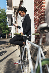 Afro young man using mobile phone and fixed gear bicycle.x
