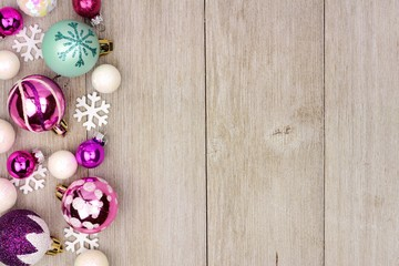 Modern pastel Christmas bauble side border over a rustic light wood background