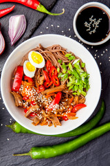 Noodles with chicken's meat, chili peppers and eggs in bowl on dark stone background. Asian Cuisine Pasta. Top view.