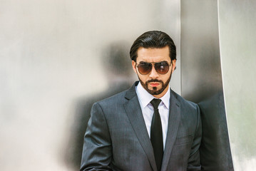 Portrait of Young Handsome American Businessman. Dressing in gray suit, white shirt, black tie, wearing sunglasses, a guy with full beard standing against silver metal wall, seriously thinking, sad..