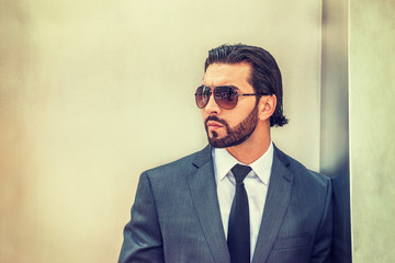 Portrait of Young Handsome American Businessman. Wearing gray suit, white shirt, black tie, sunglasses, a guy with beard standing against silver metal wall, looking away. Instagram filtered effect..