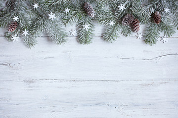 Christmas wood background with branches of Christmas tree in snow, snowflakes