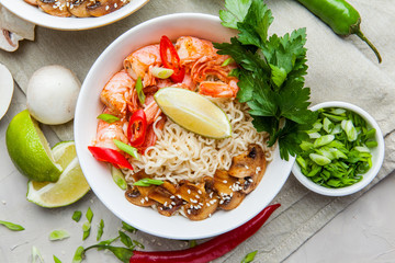 Noodles with shrimp, chili peppers and mushrooms in bowl on grey stone background. Asian Cuisine Pasta. Top view.