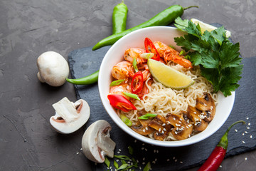 Noodles with shrimp, chili peppers and mushrooms in bowl on dark stone background. Asian Cuisine Pasta.