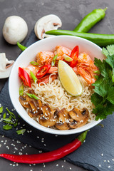 Noodles with shrimp, chili peppers and mushrooms in bowl on dark stone background. Asian Cuisine Pasta. Top view.