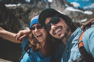 Young happy couple with backpacks taking selfie photo while climbing rocks together in stunning mountains