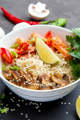 Noodles with shrimp, chili peppers and mushrooms in bowl on dark stone background.