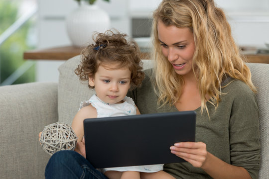 mother and daughter watching tv on tablet