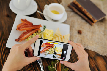 girl takes breakfast on the camera of a smartphone close-up