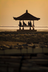 Men Sitting on a Balinese Bale Gazebo During Sunset. Sanur, Bali, has a west facing view from the beach where locals and tourist gather to enjoy the sunset in one of the many Gazebos on the coastline.