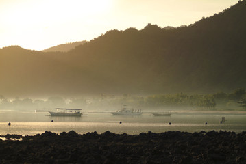 Balinese Sunrise in the Village of Pemuteran. Traditional Indonesian vessels are anchored in the bay off the village of Pemuteran during a glorious sunrise in the northwest corner of Bali, Indonesia.