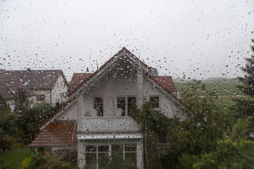 Rain drops on window glass with view to the neighbor house