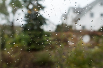 Rain drops on window glass with view to the countryside