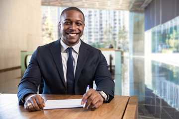 Charming warm friendly smile from stylish financial sales manager sitting at desk with paperwork