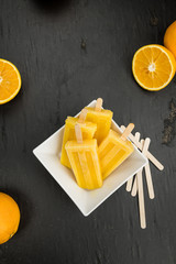 Homemade orange popsicles on a vintage background (selective focus)