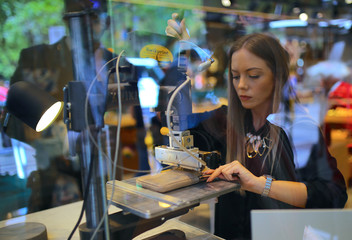 A woman uses a machine to emboss a wallet in the window of a retail store selling leather goods in central Sydney