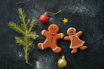 Festive Christmas background. Gingerbread man and girl cookies, fir tree, balls on a snowy black stone background. Top view.