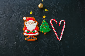 Festive Christmas background, Cookies with image of Santa, fir tree, candy canes, stars and ball on a black stone background. Top view with copy space.