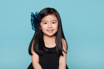 Studio portrait of asian girl with happy look in front of blue background