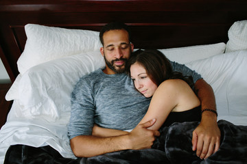 Black and white couple cuddling in bed