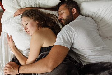 Black and white couple sleeping in bed