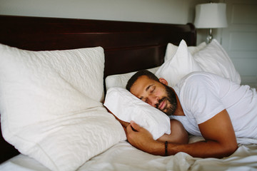 Black man sleeping in bed