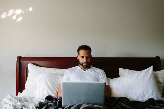 Black man working in bed with laptop computer