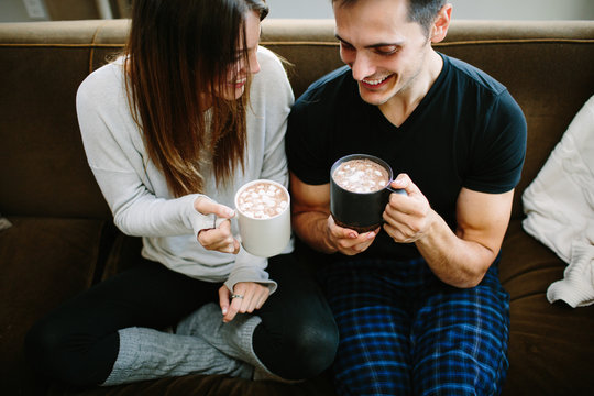 Couple sitting on the couch cuddling and drinking hot chocolate