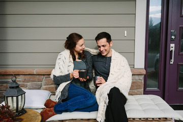 Couple in love sitting on front porch drinking coffee