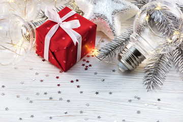christmas fir tree branch, gift box and decorative lamp bulbs on white background with confetti