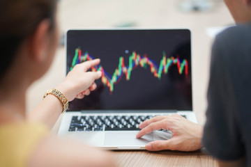 Close up business man hand touch pad on laptop for learning about stocks graph trading.two investor consulting about currency market chart concept