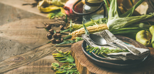 Fall table setting for Thanksgiving celebration. Flat-lay of plate, cutlery, candle holder, Autumn seasonal vegetables, fruit and fallen yellow leaves for decor over wooden background, copy space