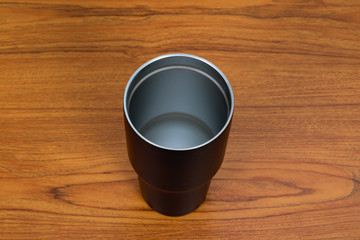 Black colour stainless steel tumbler or cold storage cup with water straw and cap on wood background.