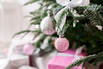 Christmas tree decorated with toys in silver and pink color. In it we see the balloons with of ribbons and lights glowing garland.