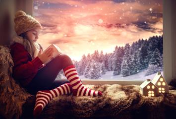 Mädchen sitzt am Fenster mit Geschenk