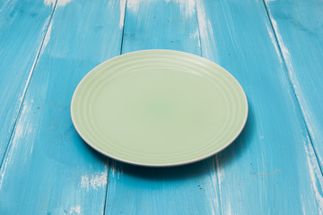 Green Round plate on blue wooden table with perspective