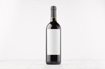 Dark wine bottle with blank white label on white wooden board, mock up. Template for advertising, design, branding identity.