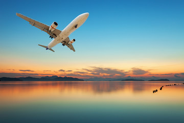 Airplane flying over tropical sea at beautiful sunset or sunrise scenery background.