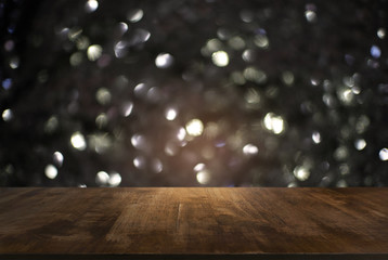 Empty wooden table in front of black and gold glitter lights background . can be used for display or montage your products.Mock up for display of product.