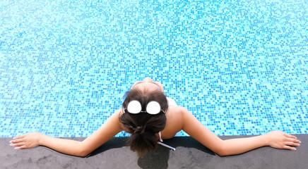 Young asian Beautiful woman relaxing in swimming pool at spa resort
