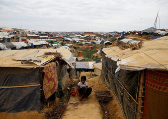 A Rohingya refugee girl sits in between the temporary shelters as she arranges firewood at Kutupalong refugee camp near Cox's Bazar