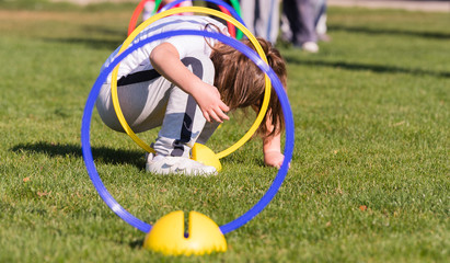 Child playing in a exercising circle - tunnel tube, crawling through it and having fun