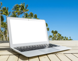 Laptop computer on wooden table. Top ocean view. Tropical island background. Open blank laptop computer empty space. Front view with copy space. Isolated white screen